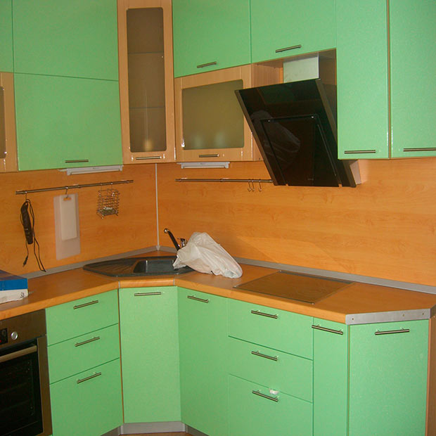 Деревянный фартук в сочетании с зеленой мебелью на кухне
