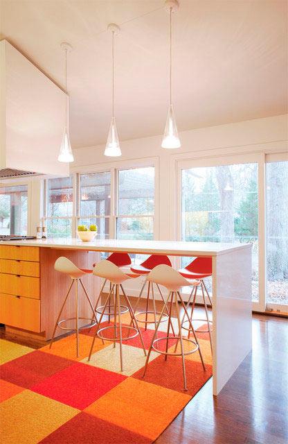 Белые стены и оранжевые аксессуары на кухне
