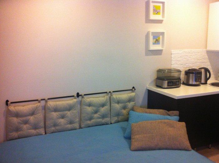 Разложенный диван и подушки на рейлинге