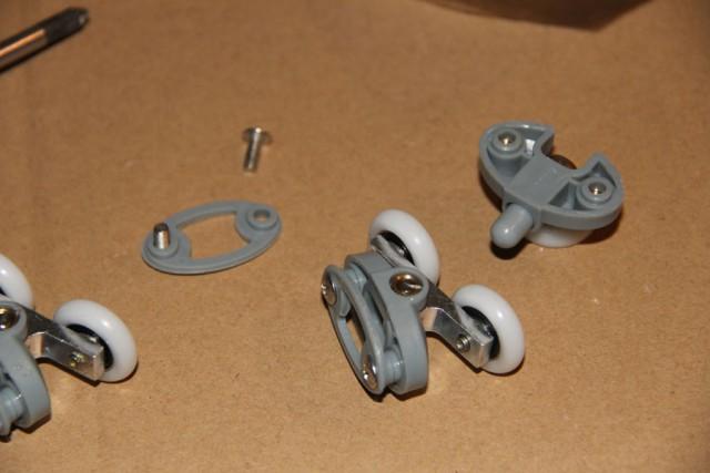 Надеваем на дверцы ролики колёсиками наружу. Ролики с кнопкой крепятся на нижнюю часть дверей (кнопка должна смотреть вверх). Регулировочные винты на верхних роликах должны смотреть вниз.